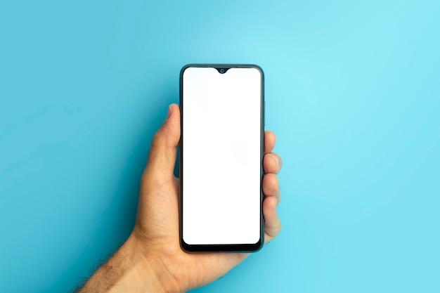 最小限の空白の画面で色付きの青いバナーの背景のモックアップ電話で手に空のスマートフォン...