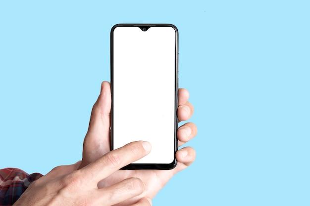 空白の画面で色付きの青いバナーの背景のモックアップ電話で手に空のスマートフォン