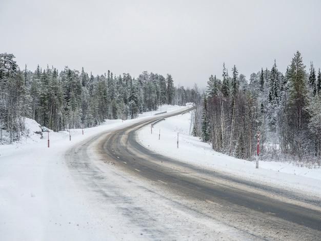 空の雪に覆われた北の冬の道、道を曲がってください。