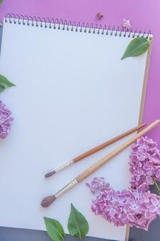 花とペイントブラシのライラックの束と空のスペースアルバムリスト