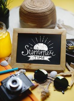 Empty space blackboard between summer beach accessories on yellow background