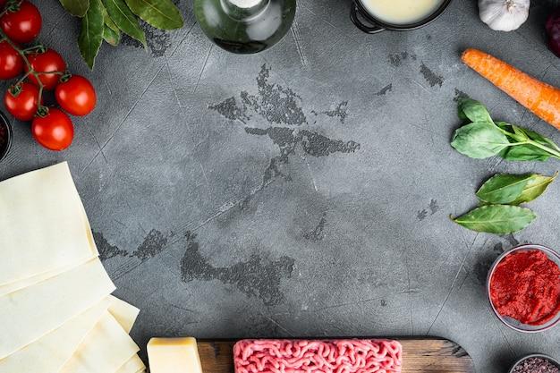 空のスペースクリーンフレームセットラザニアを調理するコンセプトイタリアの食材ラザニアシート肉ハーブトマトベシャメルソース灰色の石のテーブルトップビュー