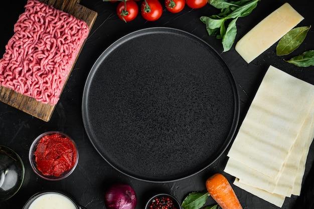 空のスペースクリーンプレートセットラザニアを調理するコンセプトイタリアの食材ラザニアシート肉ハーブトマトベシャメルソースブラックストーンテーブルトップビューフラットレイ