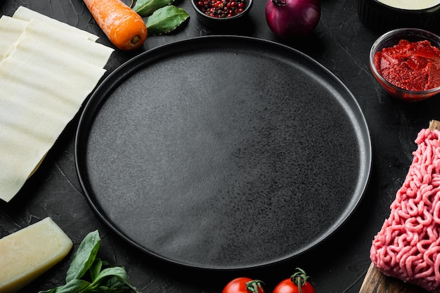 빈 공간 깨끗한 접시 세트 요리 라자냐 이탈리아 재료 라자냐 시트 고기 허브 토마토 베 샤멜 소스 검은 돌 테이블의 개념