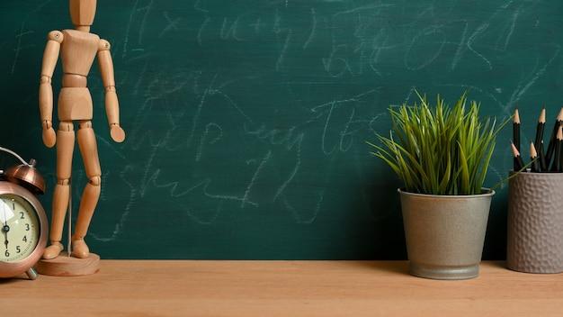 木の図、目覚まし時計、植物、緑の黒板の上に鉛筆で木製の卓上に製品を表示するための空のスペース。学習テーブルの概念