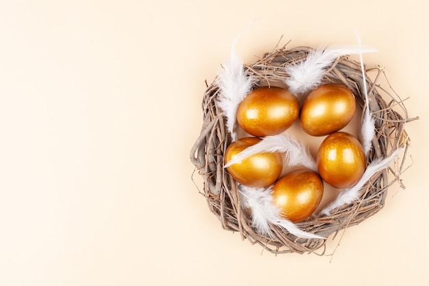 Пустое пространство для текста, знамя счастливой пасхи. расписные золотые яйца, белые перья.