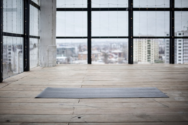 큰 창문과 천연 나무 바닥이있는 피트니스 센터의 빈 공간. 바닥에 풀린 요가 매트, 사람 없음.