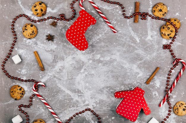 Spazio vuoto all'interno di un cerchio di spezie, biscotti, caramelle bianche rosse e ghirlanda rossa