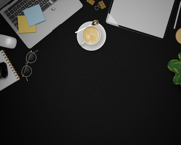 Empty space for montage on black leather background with laptop tablet mockup office supplies