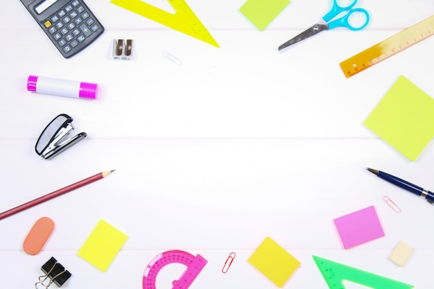 Empty space surrounded by stationery on a white wooden table. copy the space.