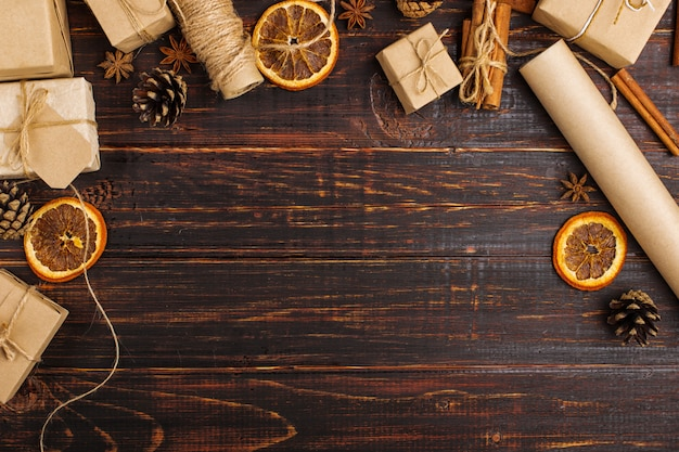 Empty space for text in the midst of gifts of dried orange, cinnamon, pine cones, anise