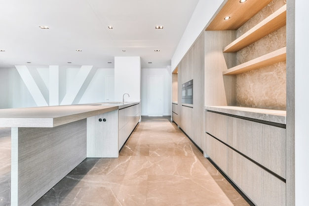 タイル張りの床の豪華なペントハウスアパートメントにある、現代的なミニマリストキャビネットを備えた空の広々としたキッチン