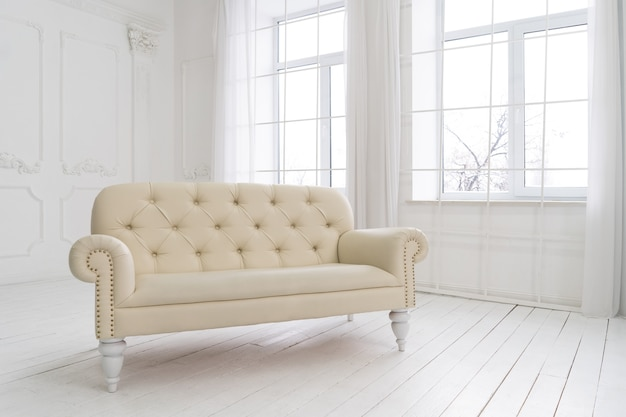 Пустой интерьер просторной комнаты с винтажным кожаным диваном на окне, белой стене и полу