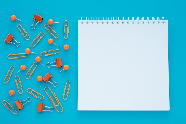 Empty spiral notebook and clips on blue background.