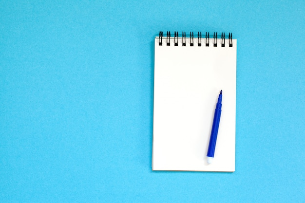 Empty spiral notebook and pen on blue