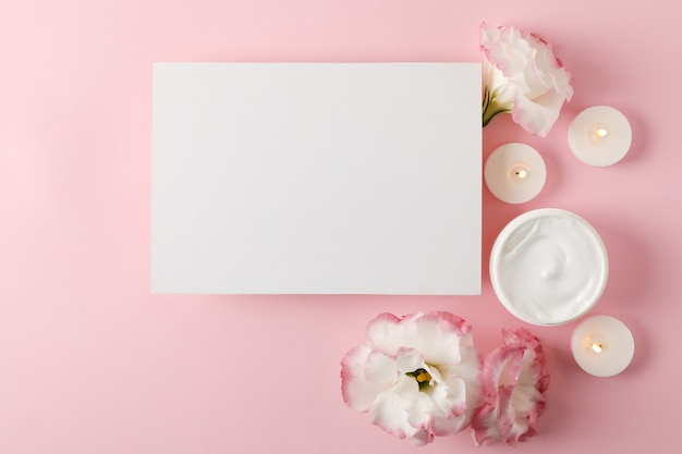 Empty square, candles, flowers and cream on pink background, space for text