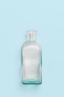 Empty square glass bottle on a light  blue wall.