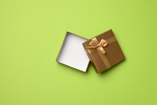 Empty square golden box with cardboard bow on green background, gift open, top view