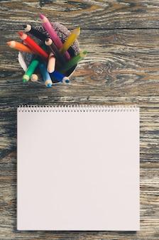 空の正方形のノートと木製のテーブルにカラフルな鉛筆のセット。白紙。