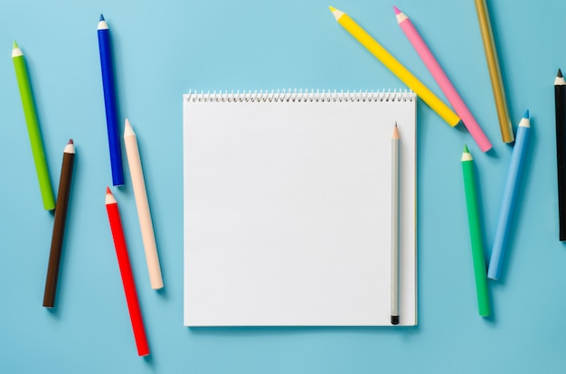 Empty square notebook and set of colorful pencils on blue background. blank paper.