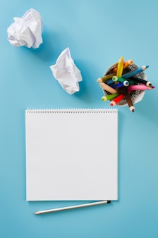 Empty square notebook, set of colorful pencils and crumpled up papers. blank paper.