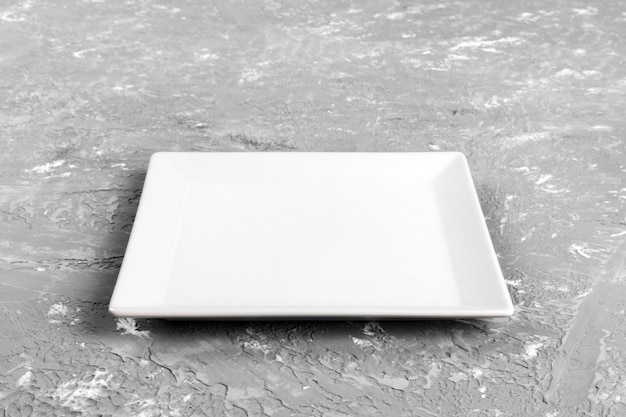 Empty square plate on cement background. perspective view