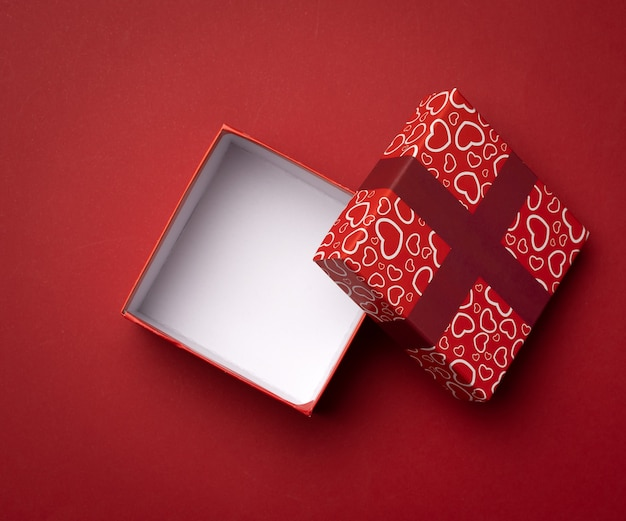 Empty square red box on a red background, gift open, top view
