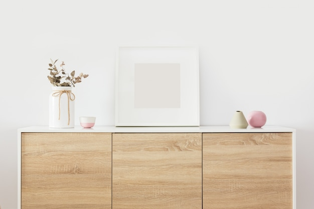 Empty square white frame in living room interior with nordic decoration