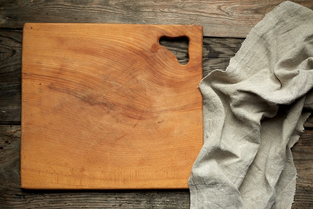 Empty square wooden kitchen cutting board and gray linen towel