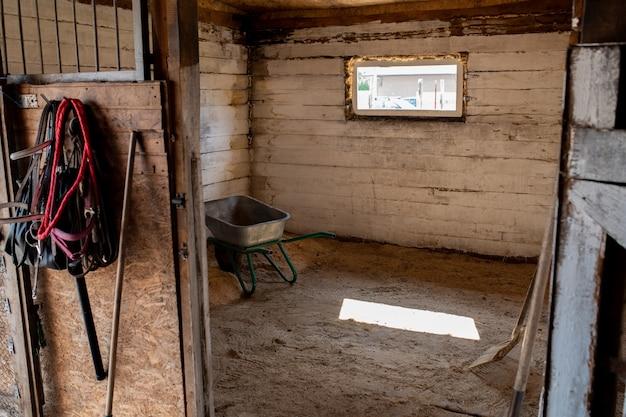 開いたドアで見ることができる小さな窓、作業工具、カートを備えた競走馬用の空の厩舎