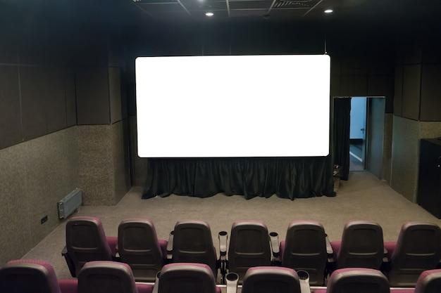 흰색 격리된 화면이 있는 작은 영화관의 빈 무대