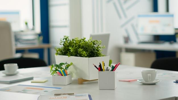 비어 있는 창업 사무실, 브레인스토밍을 위한 회의 테이블이 있는 아늑한 조명 회사실, 회의실을 위한 현대적인 디자인. 아무도 없는 금융 회사, 직장 내부 개념.