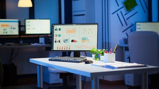 데스크탑에서 실행되는 그래픽을 사용하여 야간에 현대적인 디자인으로 비즈니스 사무실을 시작합니다. 아무도 없는 금융 회사, 작업 시작 장소, 직장 실내 개념
