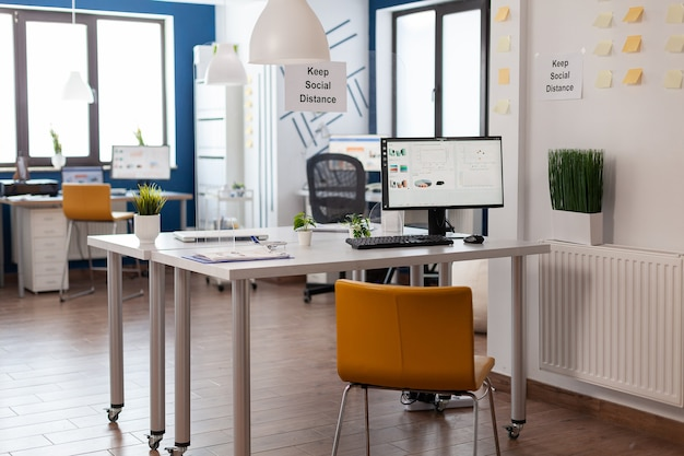 誰もいない空のスタートアップ企業のオフィスは、世界的大流行の際に金融会社の会議の準備ができています。コンピューター画面上のビジネスチャート。モダンな家具、テーブルの上のドキュメントのある職場