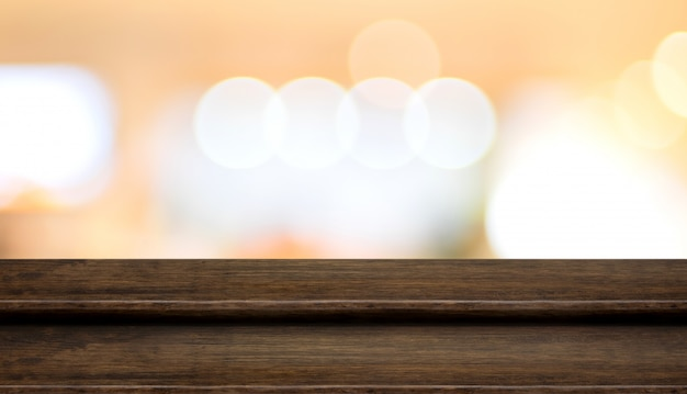 Empty step dark wood table top food stand with blur orange abstract background bokeh light