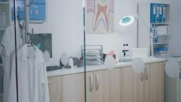 Пустой стоматологический кабинет ортодонтического госпиталя, в котором никого нет, оборудованный современной мебелью зубной ...