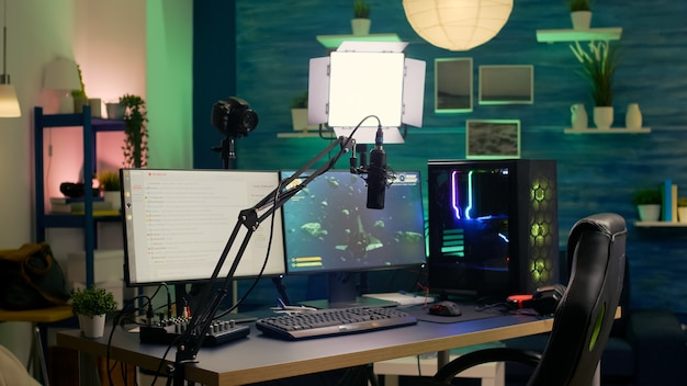 Empty streaming room with professional powerful computer, rgb keyboard and mouse, headphones and microphone