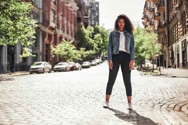 길에 서서 찾고 있는 캐주얼 옷을 입은 빈 거리의 젊은 아프리카계 미국인 여성