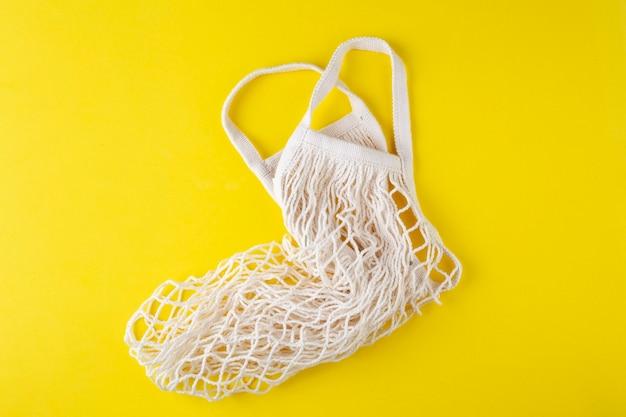 黄色の背景、上面図、エコバッグに空の文字列バッグ