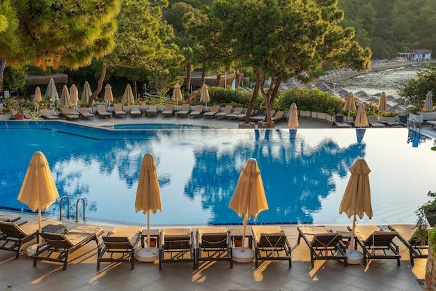 아침에 호텔 수영장 옆에 빈 선베드와 닫힌 파라솔이 있습니다. 바다 근처의 고급 호텔 리조트에 있는 수영장. 아름 다운 아침 바다입니다. 터키 보드룸