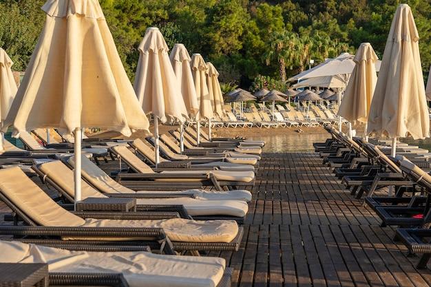 아침에 바다 옆에 빈 선베드와 파라솔이 있습니다. 바다 근처 고급 호텔 리조트의 모래 해변. 아름 다운 아침 바다입니다. 터키 보드룸