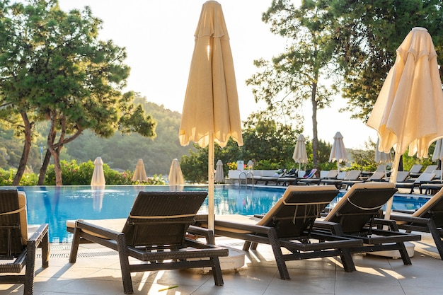 Empty sunbeds and closed parasols on morning, by the hotel pool. swimming pool in luxury hotel resort near sea. beautiful morning seascape. bodrum, turkey