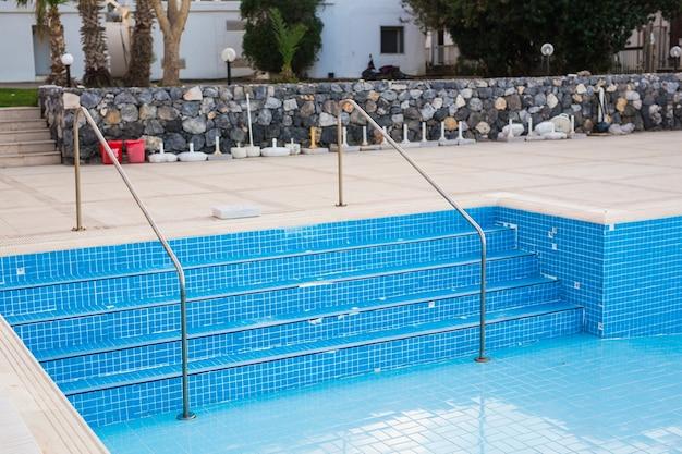 Пустой бассейн в отеле с металлической лестницей.