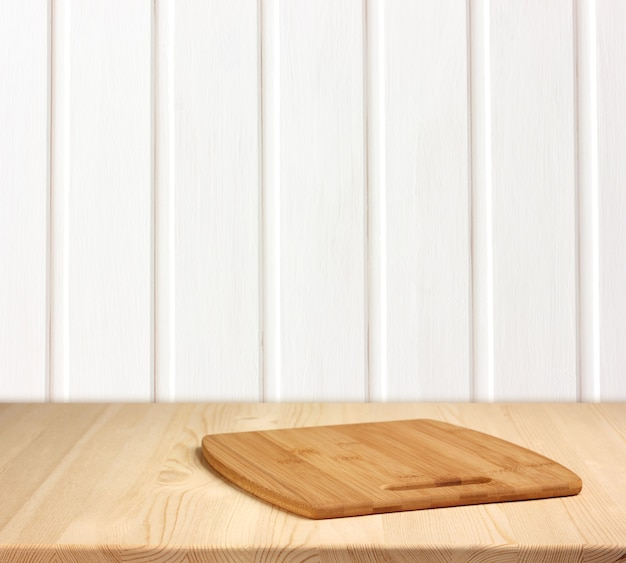 Empty table against a white wooden wall.