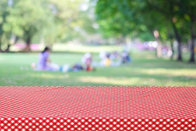 사람들이 배경 흐림 공원을 통해 빈 테이블과 빨간색 식탁보