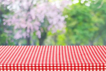 Empty table and red tablecloth with blur green leaves bokeh