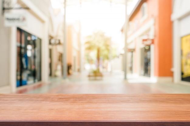 空のテーブルをぼんやりしたショッピングモールの背景