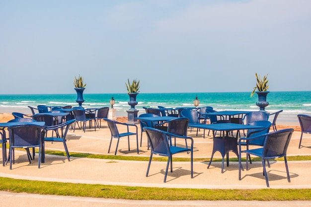 Empty table and chair around beach background