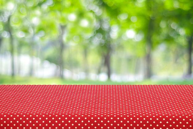 흐림 나무 배경 위에 빨간색 물방울 식탁보로 덮여 빈 테이블