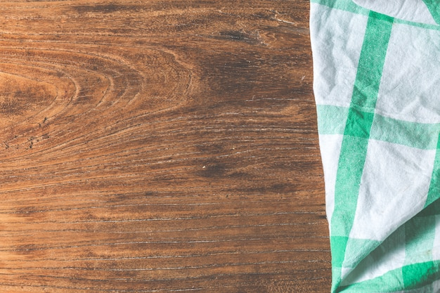 Empty table covered with tablecloth over brown cement wall background,